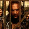 Kevin Costner in the movie Water world looking through the metal bars of the cage he is locked in.
